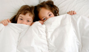 Two young girls poking there heads out from underneath a white duvet