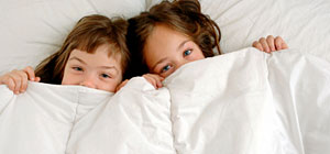 children peaking out from under a white duvet