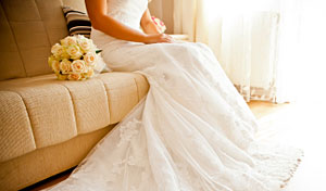 Woman in wedding dress sitting on couch with bouquet beside her