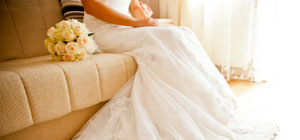woman in a white wedding dress sitting on a couch